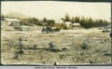 Four homes with horseteam and wagon in center of view.