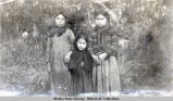Three Katalla Indian girls standing, wearing scarves.