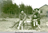 Two men sitting with two dogs and building in background.