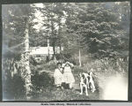 Two children and two spotted dogs on path with cabin in background.