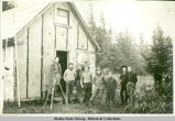 Eight men and survey equipment outside building.