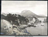 Rocky beach on east side of Whale Island and man climbing near by. July 1907 [?].