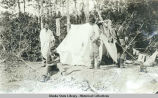 Tent with two Indians and two other men.