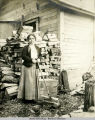 Olga Krey, age 17, standing near woodpile outside Katalla home.