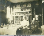 Interior of home with a man and two women sitting near table with bookshelves behind.