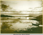 Boats in harbor silhouetted by sunset. E.W. Merrill, Sitka, Alaska.
