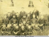 Group photo of seven men and 15 boys taken in front of the Bishop's house.