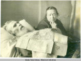 Priest Shalamov, lying on death bed; his wife seated next to him.
