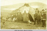 Priest standing in front of a Siberian Iakut dwelling; men, left and right. ca. 1890.