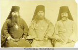 Three priests, seated; left to right.