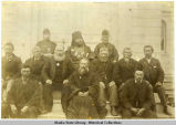 Group of twelve men at Unalaska (?) seated on church steps.