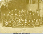 Large group of children with clergymen in second row.
