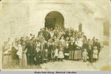 Group of men, women and children with Bishop Filip next to the Unalaska church, 1917.