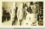 Four men standing behind an airplane motor part.