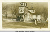 Exterior view of Russian Church at Kodiak with congregation on steps and in yard.