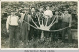 Eight men displaying an octopus, each holding a tentacle.