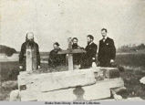 Five men standing at a cross, possible grave site.