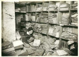Michael Vinokouroff examining stacks of records in cathedral basement.