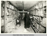 Michael Vinokouroff (sitting) and Rev. Kedroff (standing) examining shelves of Alaska records in...