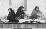 Three Alaska Native women weaving baskets.