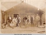 Nine men and one woman mostly dressed in vests and ties standing and sitting on porch of log cabin...