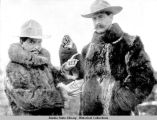 Two men wearing fur coats and brimmed hats holding large gold nuggets.