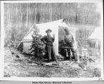 Campsite with man and woman standing in front of tent, 1900.