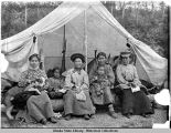 Four Native women sit on log in front of open tent, with dog and two children.
