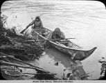 Two people in bark canoe along shore.