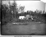 Camp site with canoe on shore, salmon drying on rack, two tents set up among trees.