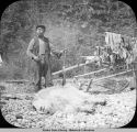 Native man stands behind dead mountain goat, holding gun.