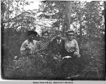 One man sits with three women in woods.
