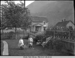 Two unidentified children in yard with picket fence. Skagway.