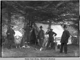Five men, some holding rifles or shovels, and goat stand in front of tent in wooded area.