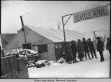 "People stand by tent-building under sign ""Seattle, Hotel."""