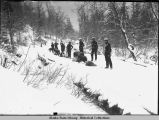 Men and dog team stand on snowy trail.