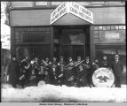 Juneau Native Band poses in snow in front of Case & Draper store front.