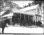 Men stand in snow in front of Reed House, Juneau.