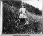 Lillian Bayers, standing in grass, about 4 or 5 yrs. old.