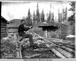 Unidentified man saws logs, sitting on special saw in unidentified settlement.
