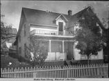 House with man sitting on steps. Picket fence in front.