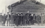 Group of eighteen men in front of a log cabin.