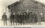 Nine men in front of log building; winter scene.
