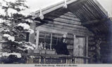 Woman on porch of log cabin; winter scene.