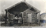 Man and woman, maybe Lorain Roberts, in front of log building.