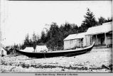 Unidentified cabin with single native canoe pulled up on beach, tents in background.