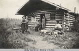 Woman (probably Lorain Roberts) and four men in front of log cabin.