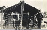 W. M. Zacharias and Tom Dodd in front of log cabin; snowshoes hanging from roof.