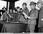Close-up of Japanese officials and Lt. Gen. Toshimoto Hoshimo as they read surrender terms.