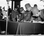 Close-up of Lt. Gen. Toshimoto Hoshimo, flanked by Japanese officials, signing surrender papers.